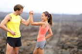 Fitness sport running couple celebrating cheerful and happy giving high five energetic and cheering. Runner couple having fun after trail cross-country running training. Asian woman, Caucasian man. poster