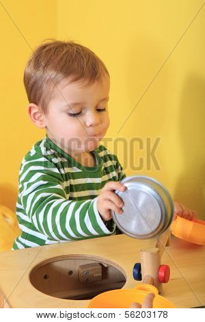 Cute caucasian toddler playing in kindergarten.