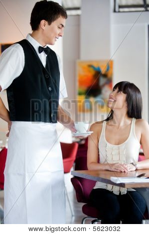 A young and attractive waiter serving coffee to a customer in an indoor restaurant poster