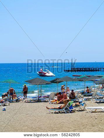 Pebble Beach And The Sea, Tourists Swim And Sunbathe