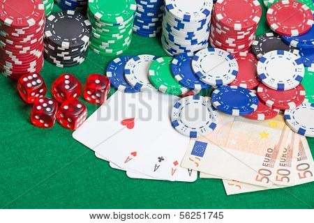 Dice, Four Aces, Colorful Poker Chips And Money On A Green Felt