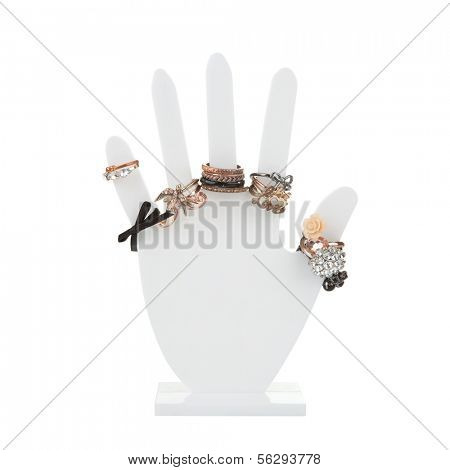 Hand-shaped jewelry holder with variety of rings isolated on white