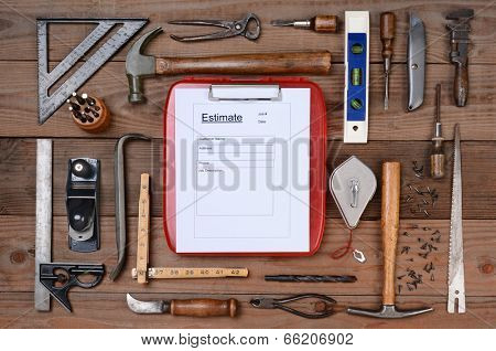 High angle shot of a contractors estimate form surrounded by his well used tools. Horizontal format on a rustic wood background.