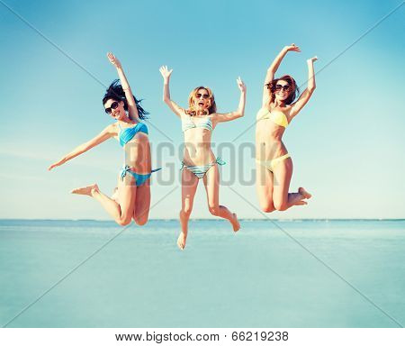 summer holidays and vacation - girls jumping on the beach