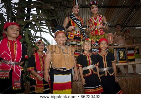 SARAWAK, MALAYSIA: JUNE 1, 2014: Children from the Bidayuh tribe, an indigenous native people of Borneo poses with the beauty pageant winners, celebrating thanksgiving day known as the Gawai festival.
