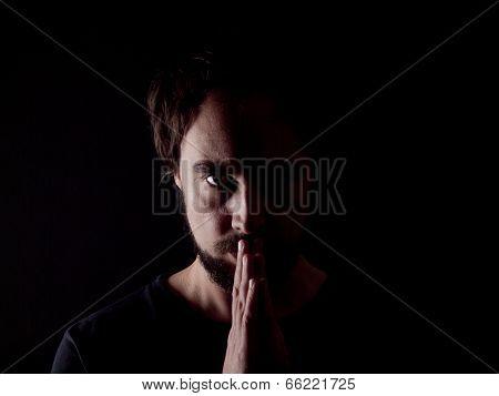 Low Key Image Of A Bearded Man Praying