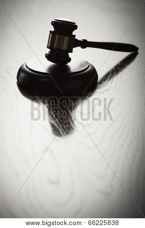Dramatic Gavel Silhouette on Reflective Wood Surface.
