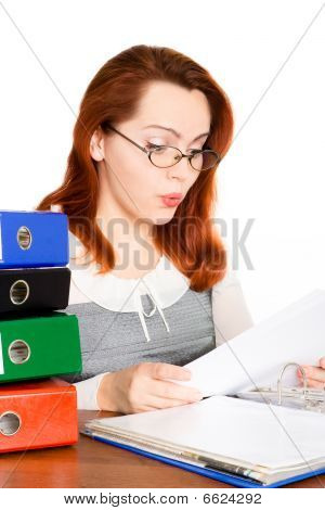 puzzled business woman in glasses looking at the paper