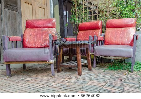 Retro Red Sofa In Front Of Old House