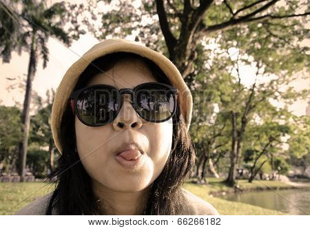 Young Naughty Woman Looking At Camera Through Sunglasses And Sticking Out Tounge, Sepia Toned