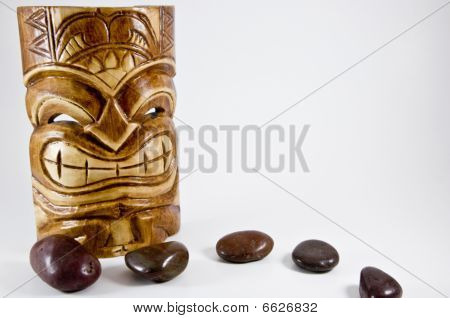 Aboriginal Tiki mask with brown pebbles path on white background poster