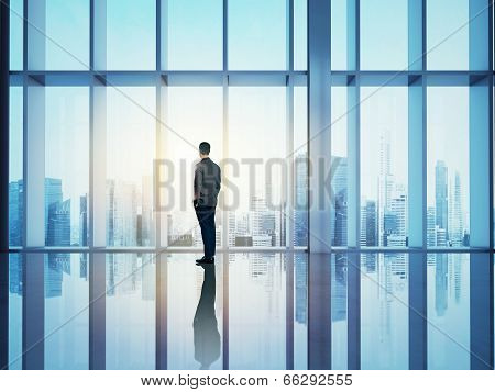 Businessman looking city through window
