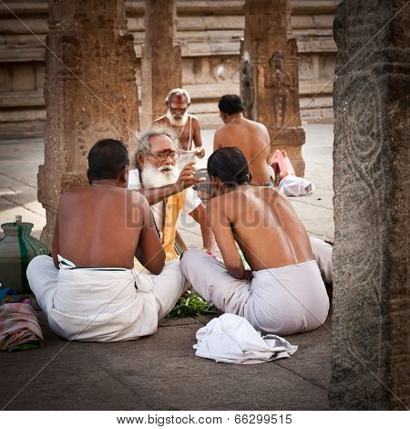 Hindu Brahmin with religious attributes providing ceremony and blessing pilgrim at Temple