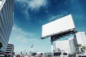 Big white blank billboard in modern city over blue sky background. poster