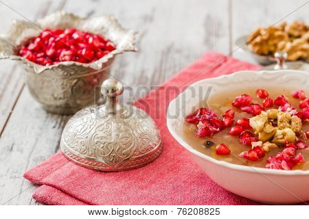 Turkish dessert Ashura Noah's pudding served with pomegranate seeds and walnuts on a white table poster
