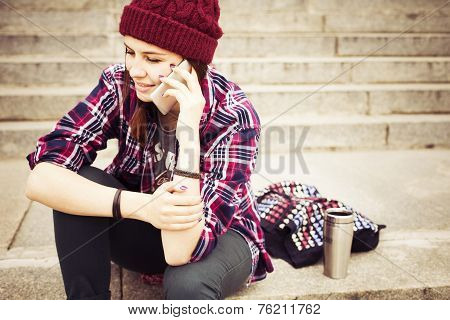 Brunette woman in hipster outfit sitting on steps and talking on the phone on the street. Toned imag