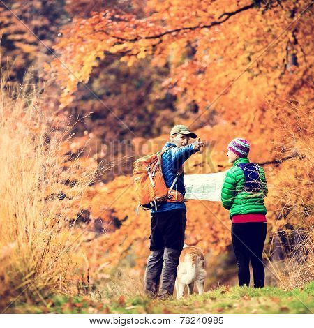 Man and woman hikers hiking in autumn colorful forest with akita dog. Young couple looking at map and planning trip or get lost vintage retro instagram style photo poster