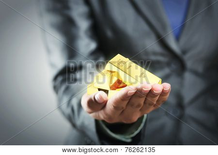 Golden bars on the woman's hand