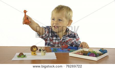 boy sculpts from plasticine animals