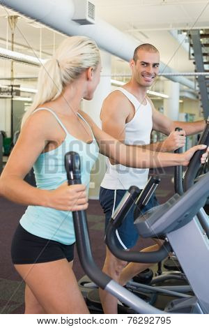 Side view of a fit young couple working on x-trainers at the gym