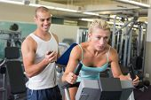 Smiling male trainer timing his client on exercise bike at the gym poster