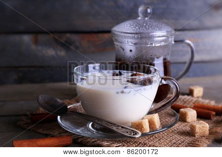 Black tea with milk in glassware and lump sugar on color wooden planks background poster