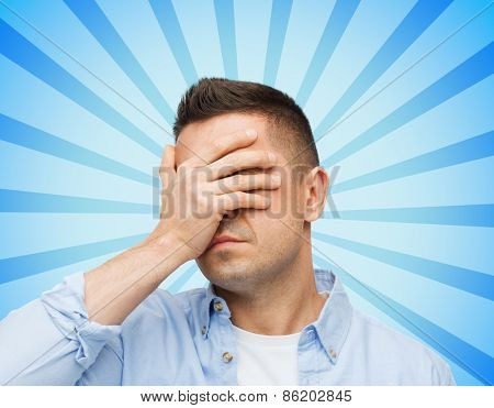 stress, headache, health care and people concept - unhappy man covering his eyes by hand over blue burst rays background
