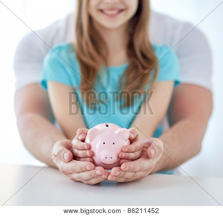 family, children, money, investments and people concept - close up of father and daughter hands holding pink piggy bank poster