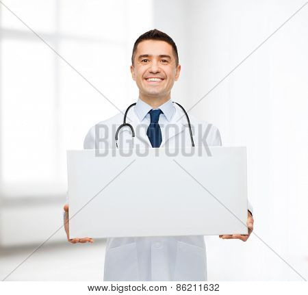 healthcare, advertisement, people and medicine concept - smiling male doctor in white coat holding white blank board over hospital room background