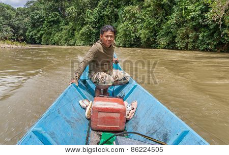 Iban Man Steering His Longboat Up The River On Borneo