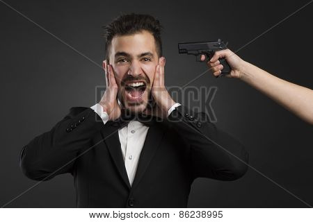 Man yelling with a weapon pointing on his head