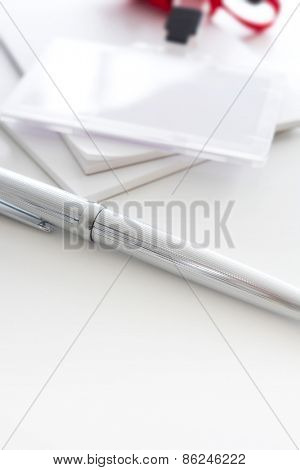 Silver pen and security or ID card with red strap. Shallow depth of field.