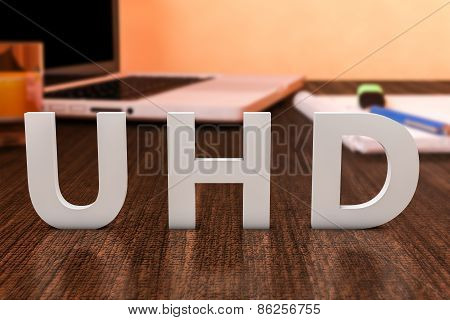 UHD - User Help Desk - letters on wooden desk with laptop computer and a notebook. 3d render illustration. poster
