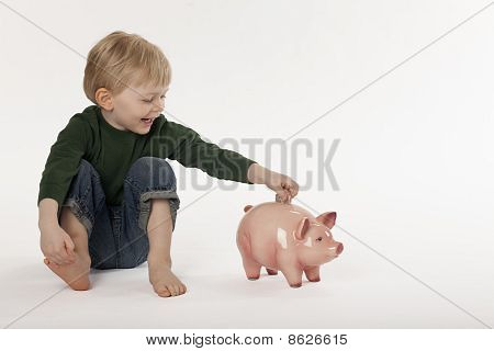 Young Boy Saving Money in a Coin Bank