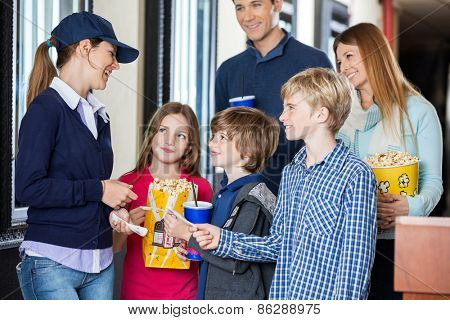 Happy young female worker checking movie tickets of family at cinema