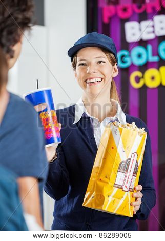 Happy female worker selling popcorn and cold drink to man at cinema concession stand