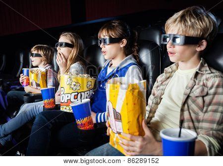 Shocked siblings having snacks while watching 3D movie in cinema theater