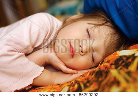 Adorable little girl sleeping in her bed