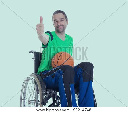 Disabled Man In A Wheelchair Is Doing Sport With Ball And Thumb Up