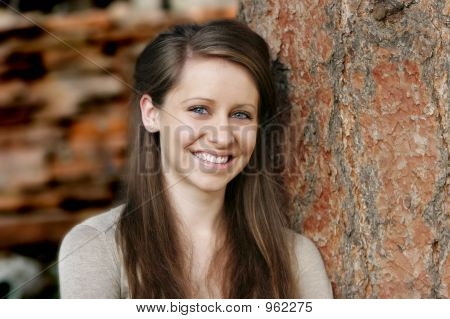 Beautiful Young Woman Against A Tree