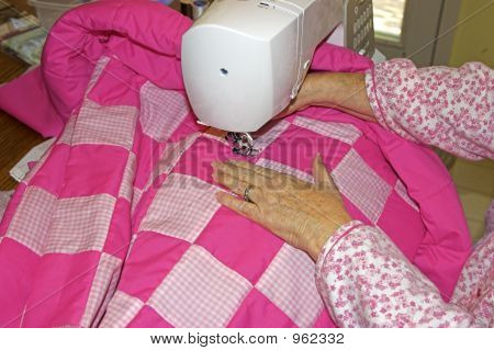 Lady Sewing A Quilt