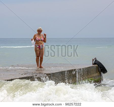 Aged Woman Is Standing Above Splashing Of Ocean Waves.