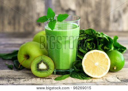 green smoothie with fruits and vegetables on wooden background