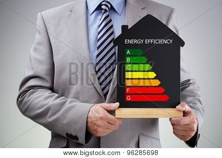 Businessman holding house shape blackboard with chalk energy efficiency rating chart concept for performance, efficiency and environmental conservation