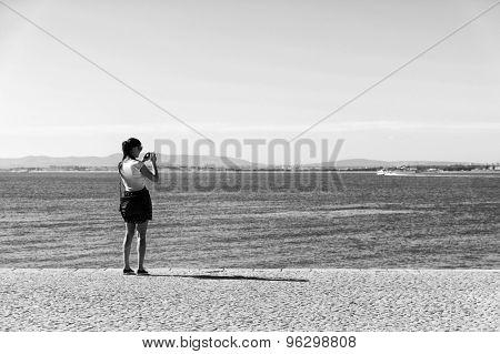 Brunette girl on the shore of Tagus, River, Portugal, Europe