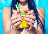 Young woman with marine sailor manicure holding glass of orange juice, summer nail art beauty and drink concept poster