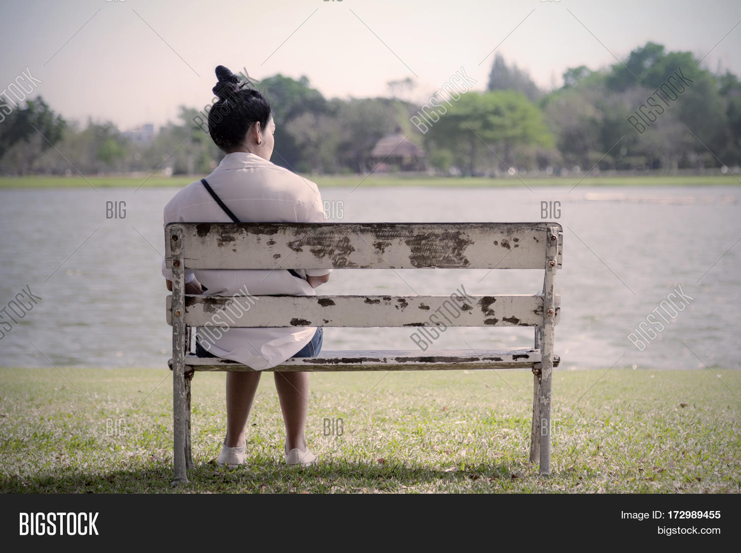 Beautiful lonely woman in frustrated depression sitting alone on bench in park concept of lonely sadness alone depressed and human problems