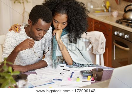 Young African-american Couple Facing Financial Problem. Unemployed Male Holding Glasses, Looking At