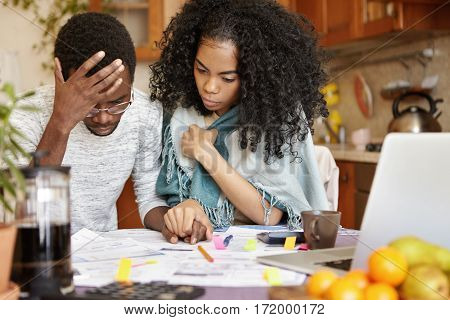 Young African-american Couple With Many Debts Calculating Gas And Electricity Bills While Doing Pape