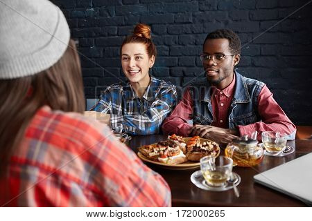 International Friendship. Fashionable African Male In Glasses Sitting At Cafe Table With Food Next T
